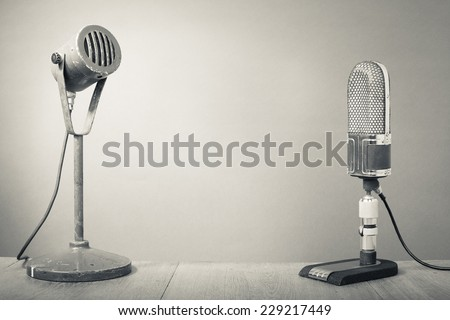 Old big retro microphones on table. Vintage style greyscale photo - stock photo