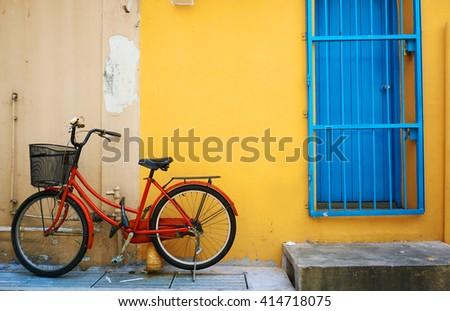 Old bike against the yellow wall - stock photo