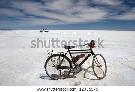 Old bike against white jeep parked on the famous Salar Uyuni landmark. Bolivia - stock photo