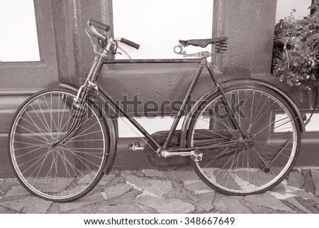 Old Bike on Red and White Building Facade in Black and White Sepia Tone