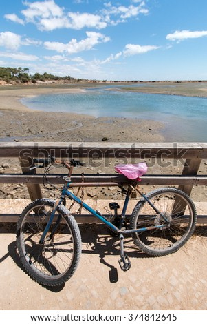 Old bike parked to a view of the Ria Formosa marshlands located in the Algarve, Portugal. - stock photo