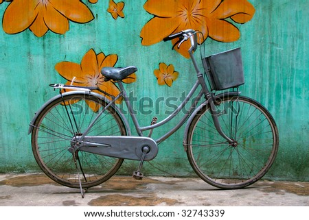 Old bike with a basket against a colourful wall. - stock photo