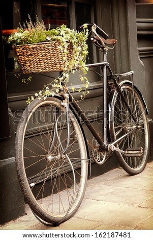 Old bike with flowers in the shopping basket, leaning against the outside of a building. Retro style processing processing with intentional vignette. - stock photo