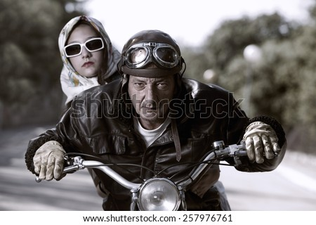 Old biker with helmet and goggles, accompanied by a woman with glasses and headscarf - stock photo