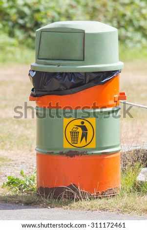 Old bin, green and orange, keeping nature clean - stock photo