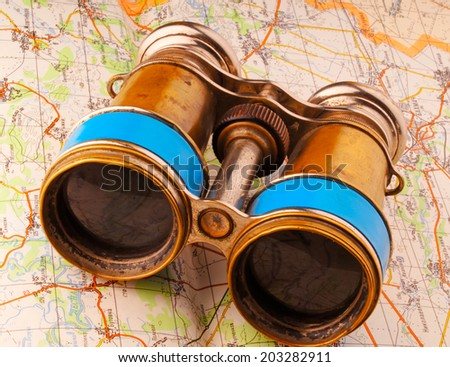 old binoculars lies on the automotive map - stock photo