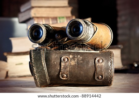 Old binoculars on an old map: an explorer planning the next expedition. - stock photo