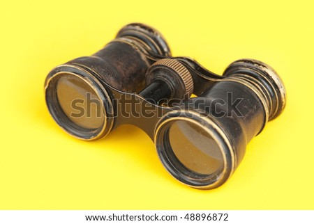 Old binoculars on yellow background - stock photo