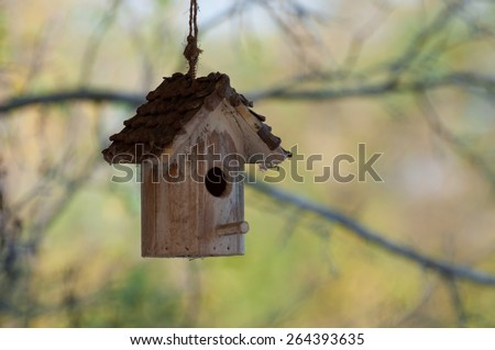 old bird house hanging amidst branches - stock photo