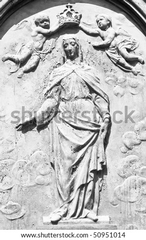 Old black and white image in of the Virgin with two angels putting to him a crown - stock photo