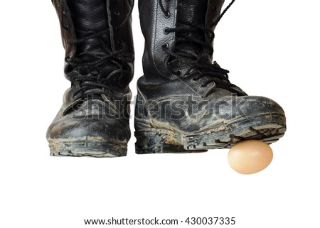 Old black army boots trampling egg. The egg as a symbol of the beginning, emotional shot. Focus on the egg and the sole of the right shoe. - stock photo