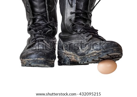 Old black army boots trampling egg. The egg as a symbol of the beginning, emotional shot. Focus on the egg and the sole of the right shoe - stock photo