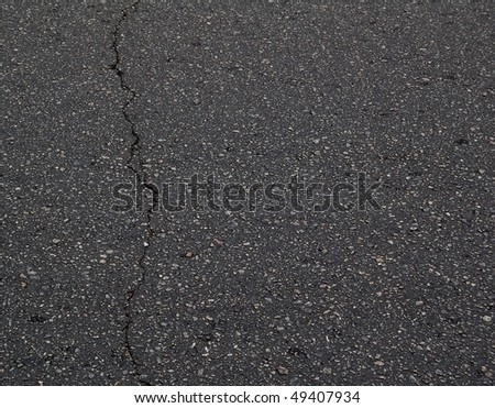 Old Black Asphalt Texture with a Crack. Asphalt Background with Space for Text. - stock photo