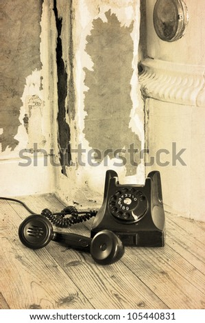 Old black bakelite phone on the floor in a grungy house with the receiver off. - stock photo