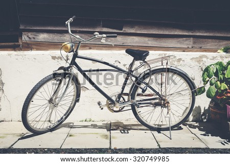 Old black bicycle with house wall background