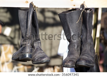 Old black boots hang by shoelaces on military camp / pairs of old boots hanging in a military camp - stock photo