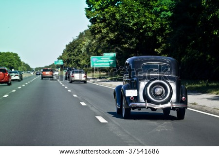 Old Black Car Driving - stock photo