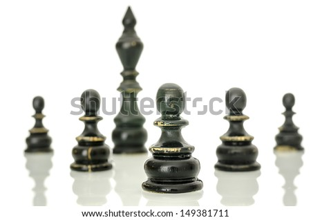 Old black chess figures. King and pawns. Isolated over white background.