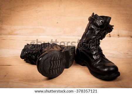 old black combat boots on wooden background - stock photo