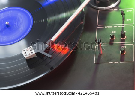 Old black gramophone during playing colorful vinyl plate lighting by colored light. Creative close up product macro photography by using long time exposition.