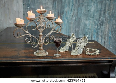 Old black grand piano with burning candles in candlestick, glass of red wine, high-heeled shoes and necklace on lid in room with ragged walls. - stock photo