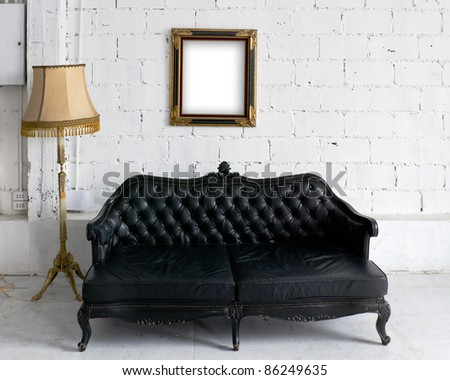 Old black leather sofa with lamp and wood picture frame on white wall