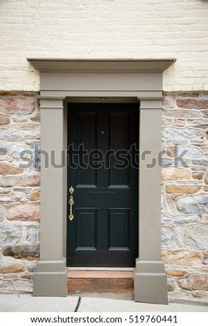 Old black painted wooden door with brass handle in Colonial architecture with a plain carved stone surround set into a natural rock wall changing to bricks at the level of the lintel
