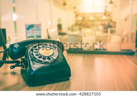 Old black phone with dust and scratches, blur coffee shop background, retro style concept - stock photo