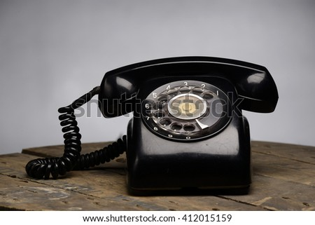 Old black phone with dust and scratches, isolated on wooden retro floor - stock photo