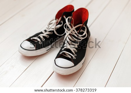 Old black sneakers with red on wooden background - stock photo