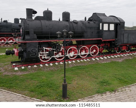 Old black steam locomotive on cloudy sky background