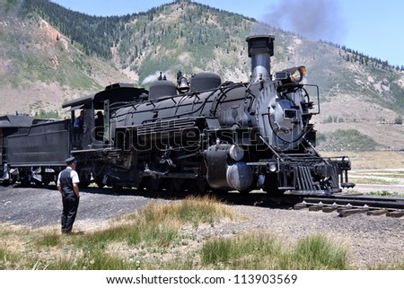 Old black steam train and conductor standing by in Colorado. - stock photo
