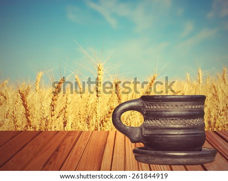Old black tea mug on wooden surface against of golden wheat ears and blue sky. - stock photo