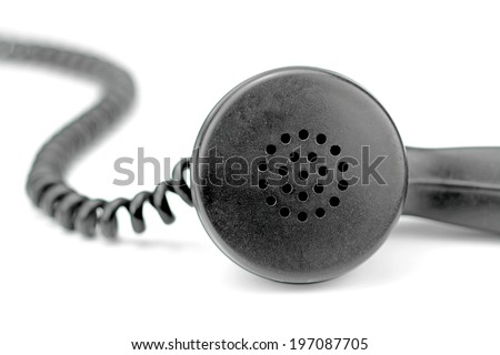 Old black telephone receiver with cord on white background - stock photo