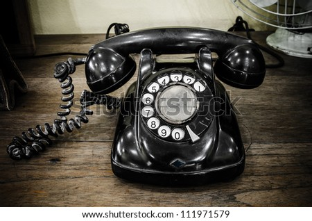 old black telephone with rotary disc - stock photo