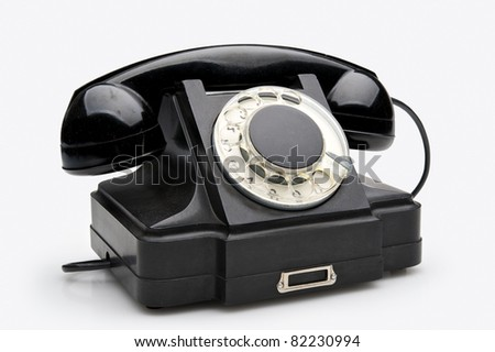 Old black vintage rotary style telephone isolated over a white background - stock photo