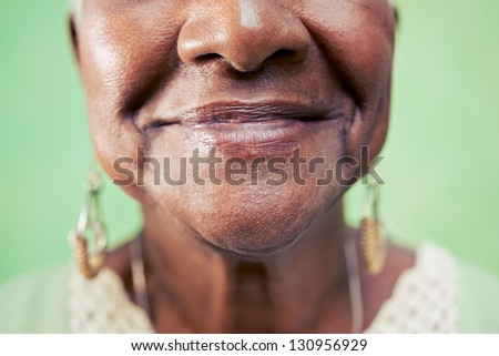 Old black woman portrait, close-up of eye and face on green background. Copy space - stock photo