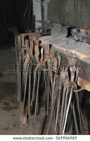 Old blacksmith tools in the  manufactory. - stock photo