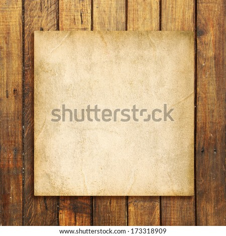 Old blank paper on brown weathered wooden background - stock photo