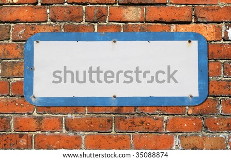 Old blank sign on a red brick wall. - stock photo