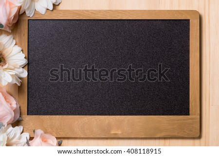 Old blank vintage school slate or chalkboard lying on an old wooden background with flowers in the corner ready for your text or message - stock photo