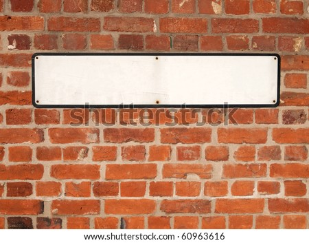 Old blank white British street sign on a red brick wall. - stock photo