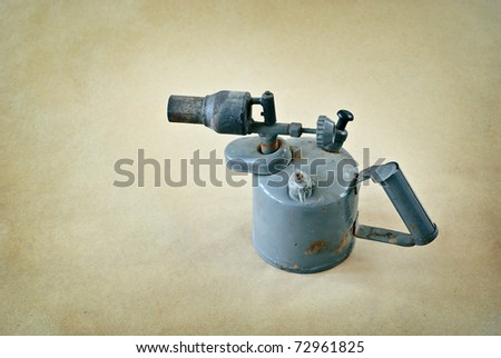 Old blowtorch on a paper background