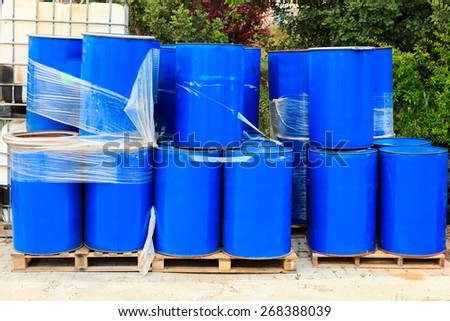 Old blue barrels standing on wooden pallets on a chemical plant - stock photo