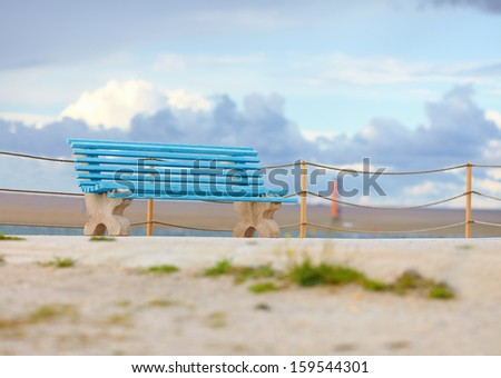 old blue bench on cloudy background