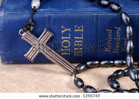 Old Blue Bible And Metal Cross On Prayer Rosaries Beads - stock photo