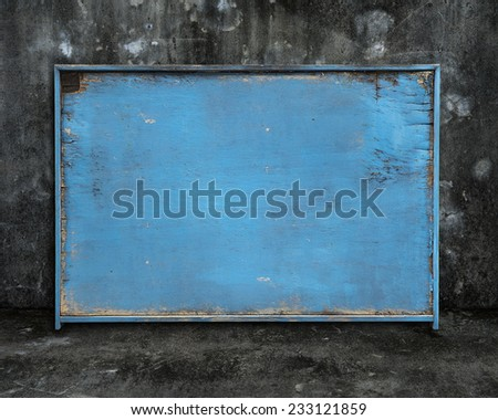 old blue blank weathered wooden board on dark mottled concrete wall and floor background - stock photo