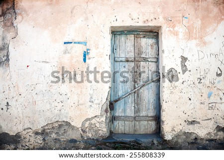 Old blue door of a abandoned house - stock photo