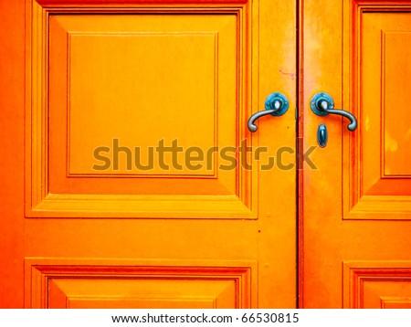 Old Blue handle on orange wood door - stock photo