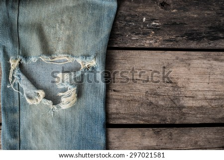 old blue jeans that is a bit torn on wood background - stock photo